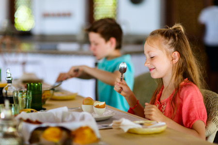 bacon portrait: Kids eating eggs for a breakfast in restaurant or at home