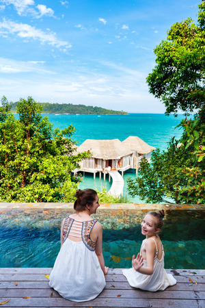 summer holidays: Happy mother and her adorable little daughter outdoors near infinity swimming pool at tropical resort