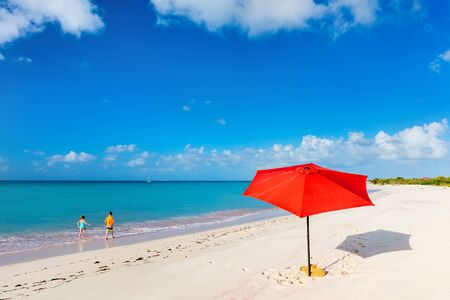 Red umbrella on Idyllic tropical beach with white sand and turquoise ocean water at deserted island in Caribbean