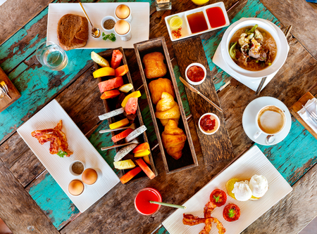 delicious food: Top view of delicious organic food served for breakfast on rustic wooden table. Coffee, eggs, fruits, juice, croissants and jam flat lay.