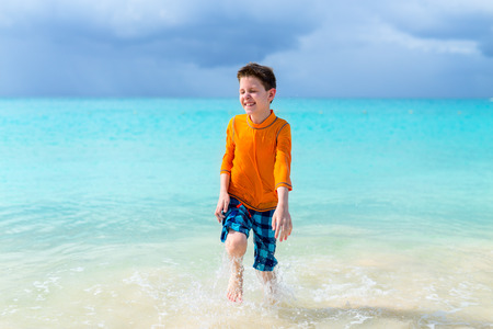 sun protection: Cute boy in sun protection rash guard at tropical beach on summer vacation