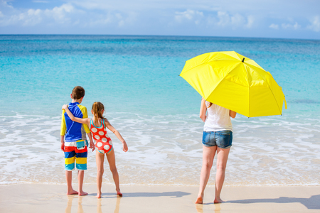 family vacation: Family mother and kids enjoying tropical beach vacation Stock Photo
