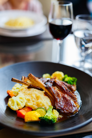 Delicious lunch or dinner with lamb cutlets and red wine in a restaurant