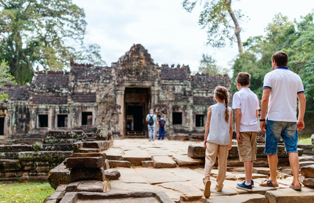 Family of father and kids at ancient Preah Khan temple in Angkor Archaeological area in Cambodia