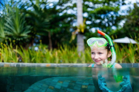 snorkelling: Adorable little girl with snorkeling equipment in a water during summer vacation Stock Photo