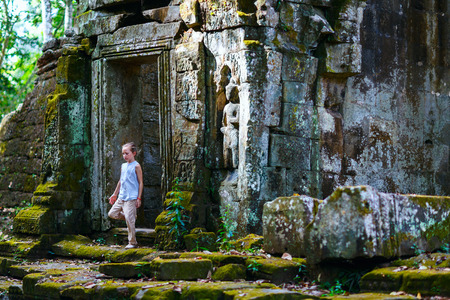 Little girl at ancient Preah Khan temple in Angkor Archaeological area in Cambodia Banco de Imagens