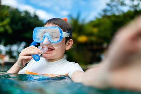 Cute boy with snorkeling equipment making selfie in a water enjoying summer vacation Stock Photo