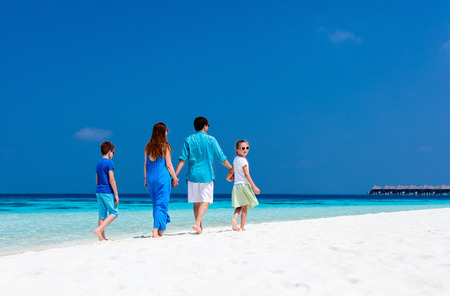 Back view of a beautiful family on a beach during summer vacation photo