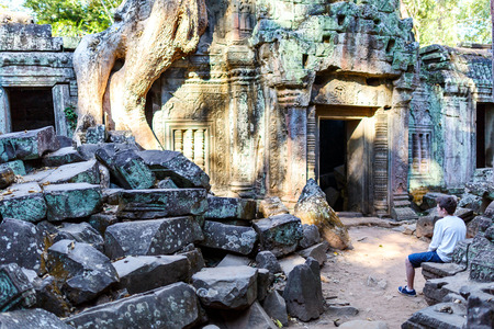 Teenage boy in Ta Prohm jungle temple in Angkor Archaeological area in Cambodia Stock Photo