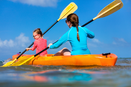 Family of mother and daughter paddling on kayaks at tropical ocean water during summer vacation