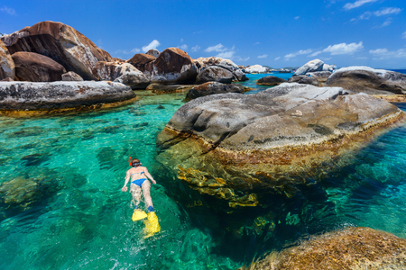 Young woman snorkeling in turquoise tropical water among huge granite boulders at The Baths beach area major tourist attraction on Virgin Gorda, British Virgin Islands, Caribbean Stock Photo