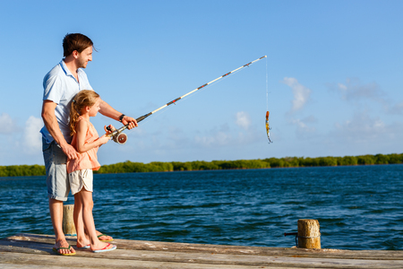 Family father and daughter fishing together from wooden jetty