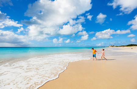 カリブ海で熱帯のビーチで楽しんで子供たち夏の休暇は、浅瀬で一緒に遊んで