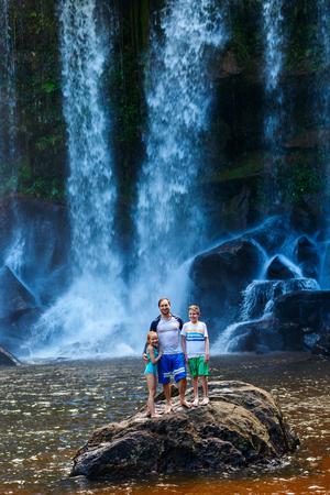 Family swimming at waterfall in Phnom Kulen National Park near Siem Reap in Cambodia