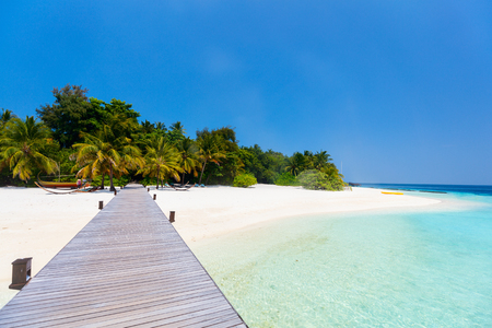 Wooden pathway leading to beautiful tropical island Stock Photo