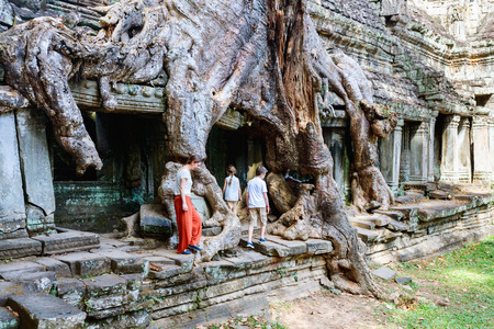 Family mother and kids at ancient Preah Khan jungle temple in Angkor Archeological area in Cambodia Stock Photo
