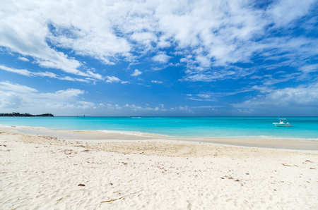 Idyllic tropical beach with white sand, turquoise ocean water and blue sky at Antigua island in Caribbean Stock Photo