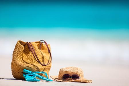 Strohoed, zak, zonnebril en wipschakelaars op een tropisch strand Stockfoto