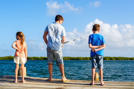 Family father and kids fishing together from wooden jetty photo