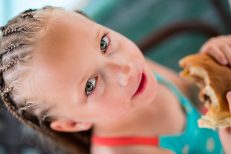Casual portrait of little girl with Caribbean braids outdoors on summer day Stock Photo