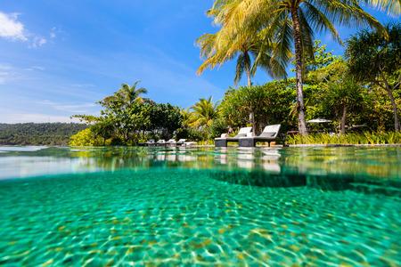 Split underwater photo of a beautiful swimming pool in luxury resort Stock Photo