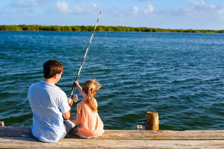 Family father and daughter fishing together from wooden jetty photo