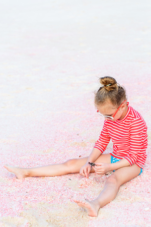 Adorable little girl playing with sand and shells on unique pink sand beach on Barbuda tropical island in Caribbean Фото со стока