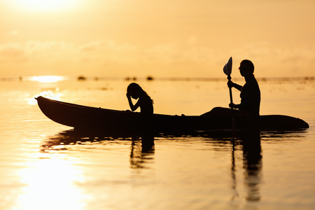 Silhouettes family of mother and daughter paddling on kayak at tropical ocean at sunset photo