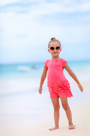 Adorable little girl at tropical white sand beach photo