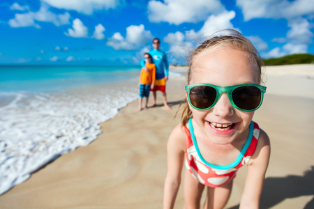 Little girl and her family father and brother enjoying beach vacation in Caribbean photo