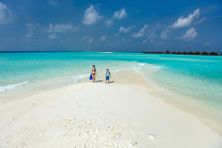 Above view of  mother and son walking at shallow turquoise ocean water with snorkeling equipment photo