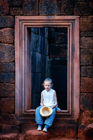 Little girl in ancient Banteay Srei temple in Siem Reap, Cambodia