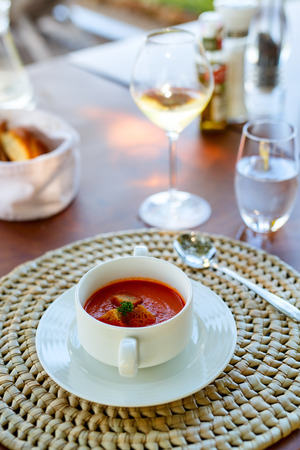 Bowl of delicious tomato soup with garlic bread and white wine served for lunch in a restaurant