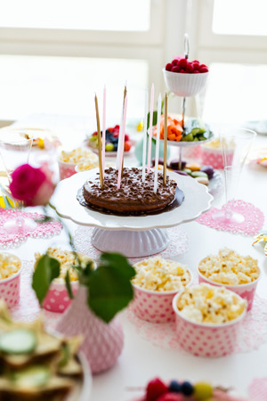 Cake, candies, marshmallows, popcorn, fruits and other sweets on dessert table at kids birthday party