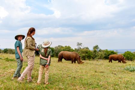 Back view of family on safari walking close to  white rhino Stock Photo