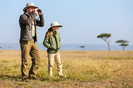 game drive: Family of father and child on African safari vacation enjoying bush view