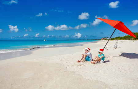 Kids in red Santa hats having fun at tropical beach during Christmas vacation playing together with sand Stock Photo