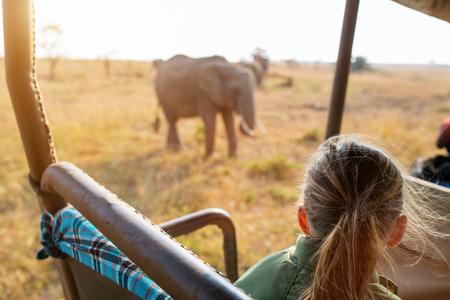 Adorable little girl in Kenya safari on morning game drive in open vehicle