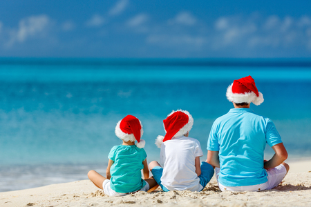 Back view of father and kids wearing red Santa hats enjoying beach vacation on Christmas Stock Photo