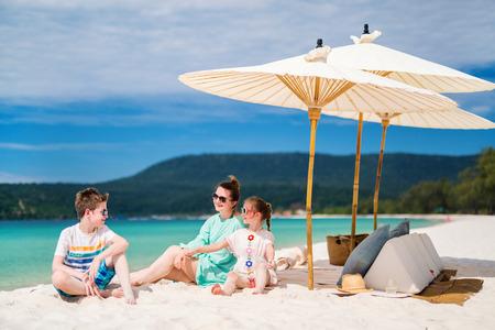 ホストファミリーのお母さんが、熱帯のビーチでの休暇を楽しむ子供達