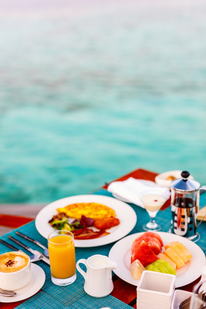 Delicious organic fruits, eggs, juice and coffee served for breakfast at tropical ocean edge in a luxury resort Stock Photo
