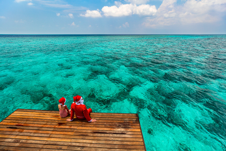 Christmas Santa Claus and little girl enjoying xmas travel vacation at tropical ocean