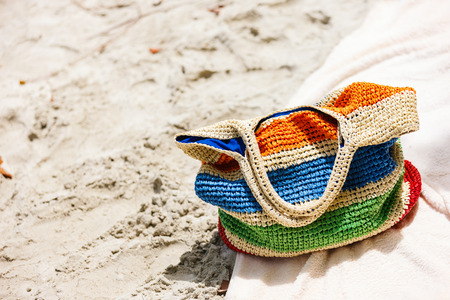 Beach vacation close up. Straw bag with towels on at tropical coast