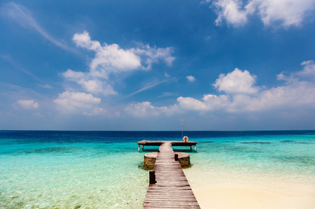 Wooden jetty and turquoise waters of tropical ocean