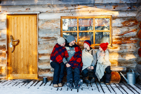 Family with kids outdoors on beautiful winter day in front of log cabin vacation house Stockfoto