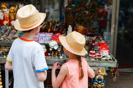 Hintere Ansicht von Bruder und Schwester von zwei Kindern am Flohmarkt Standard-Bild - 87397239