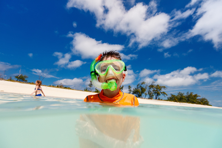 Happy boy with snorkeling mask in turquoise tropical ocean water Stock Photo