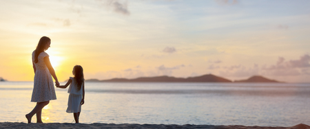 Silhouettes of mother and daughter walking along tropical beach during sunset, panorama with copy space perfect for banners Banque d'images