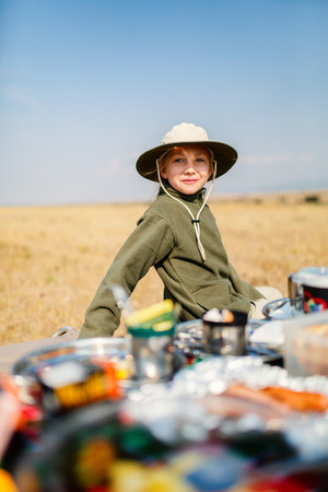 Adorable little girl in Kenya safari enjoying bush breakfast
