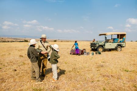 Familie van vader en kinderen op Afrikaanse safarivakantie genieten van bush ontbijt